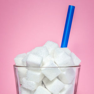Glass full of sugar cubes on a pink background with a blue straw