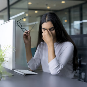 tired woman rubbing her eyes while working