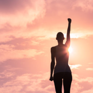 woman raising her arm in victory at sunset