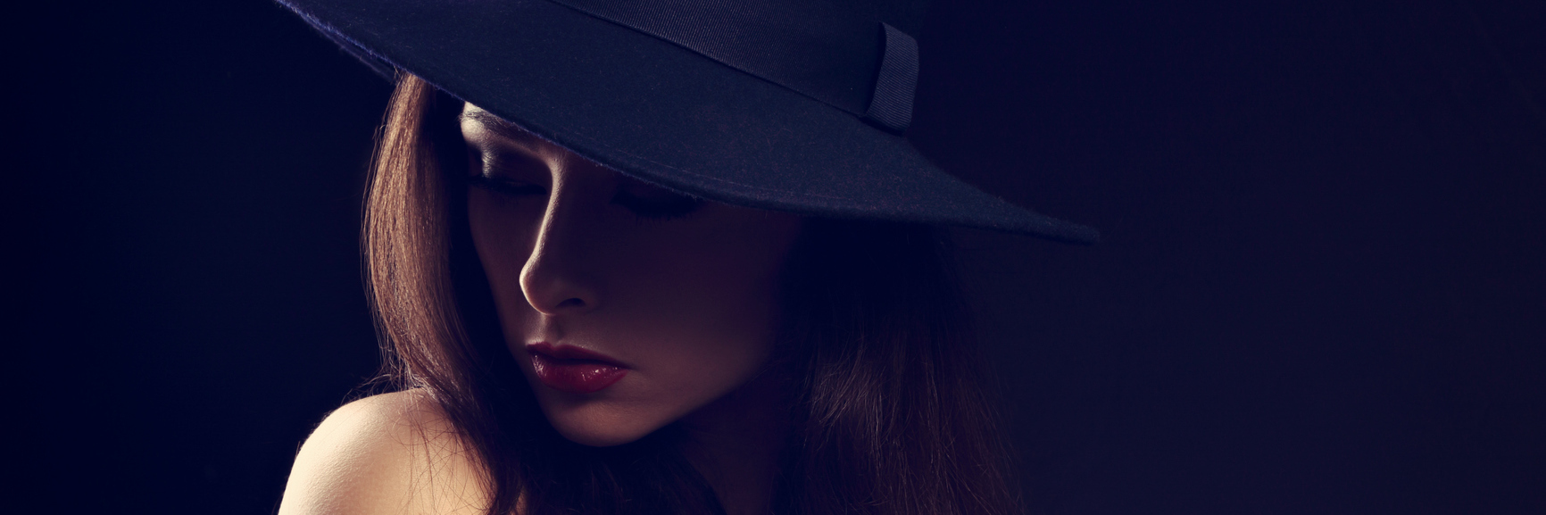 A woman wearing a hat, looking down, while surrounded by darkness.