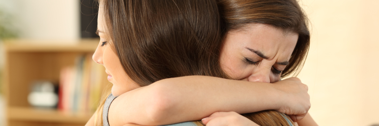 Two friends hugging, crying together.