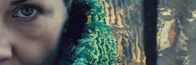 Double exposure portrait of a woman in green shawl combined with water ripples