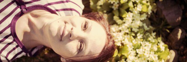 young woman lying in sunny garden looking content