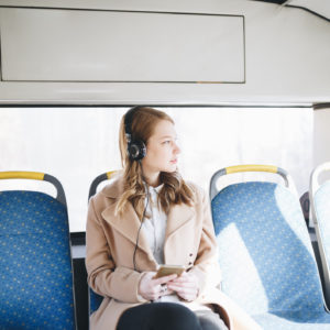 woman sitting on a bus and listening to music