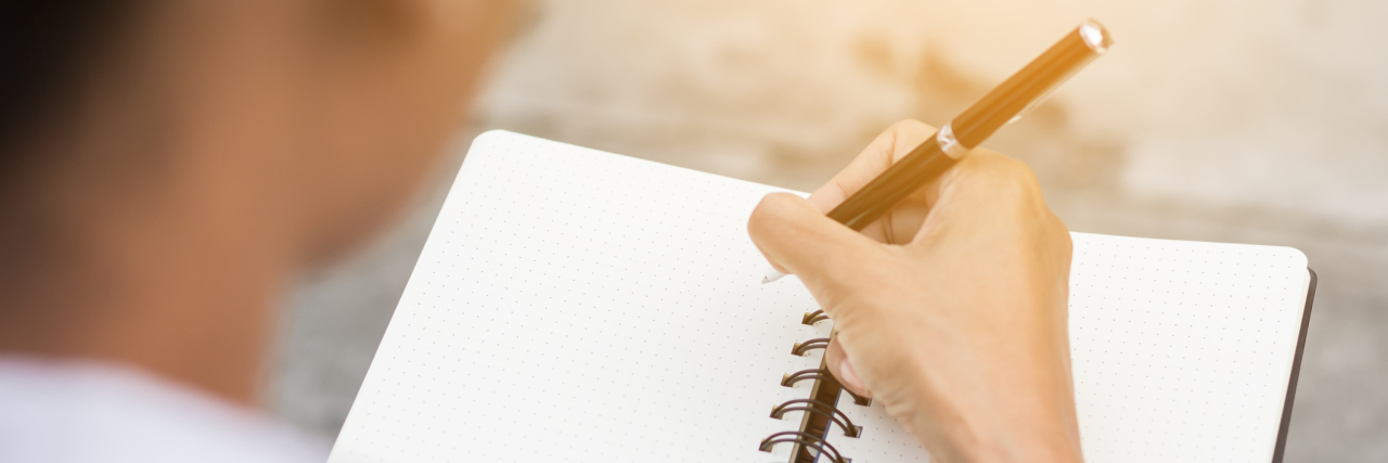 A woman writing somethings in a notebook.