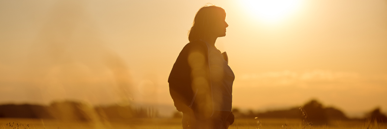 woman standing in a sunlit field