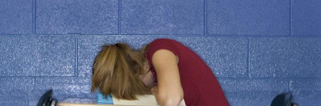 Teenage girl with head down on desk