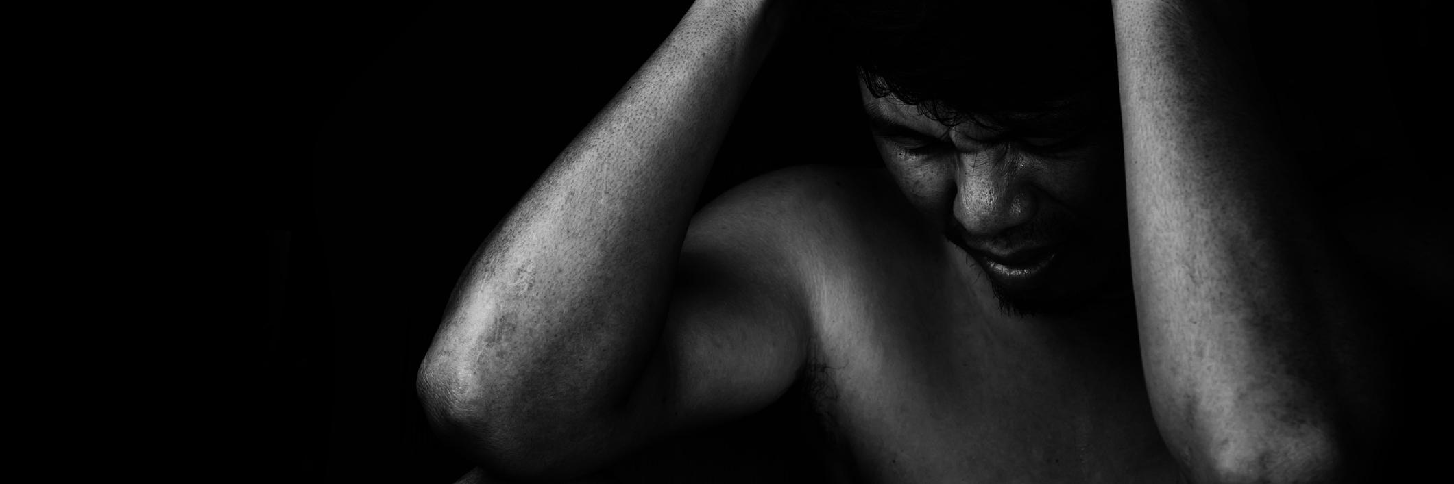 man in darkness looking depressed