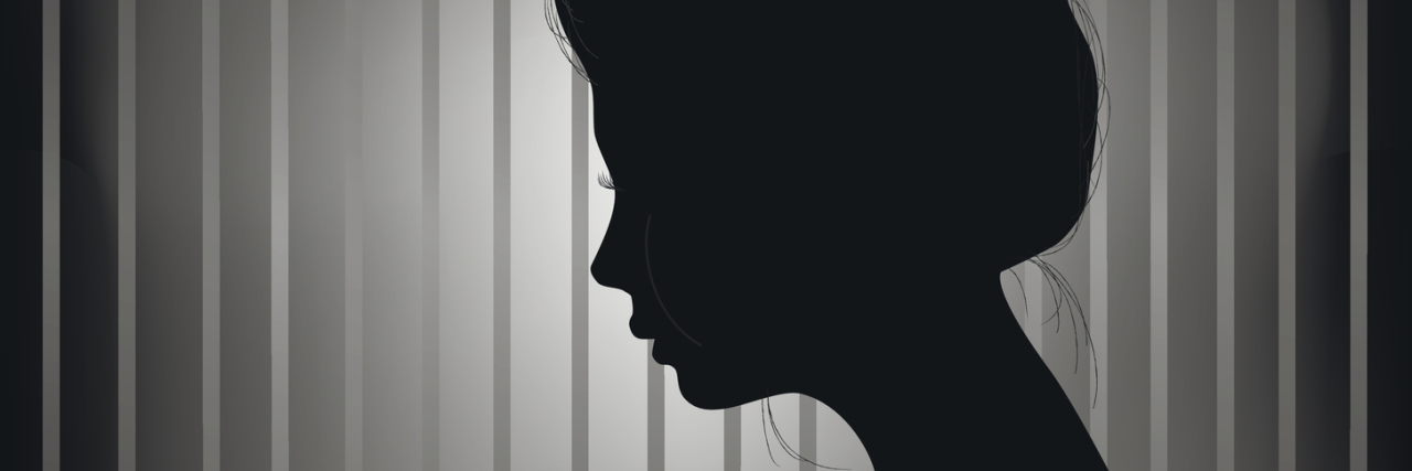 silhouette of a woman standing in front of a grey striped wall