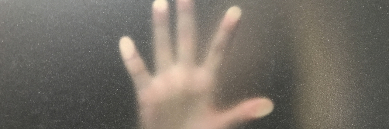 A hand blurred behind a window.