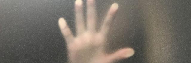 A hand blurred behind a window.