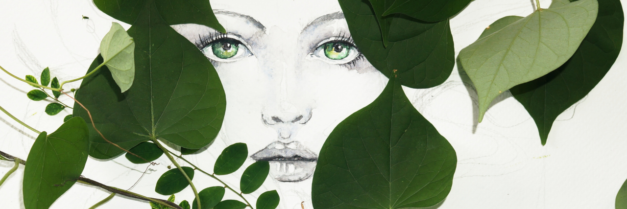 drawing of woman's face between green leaves