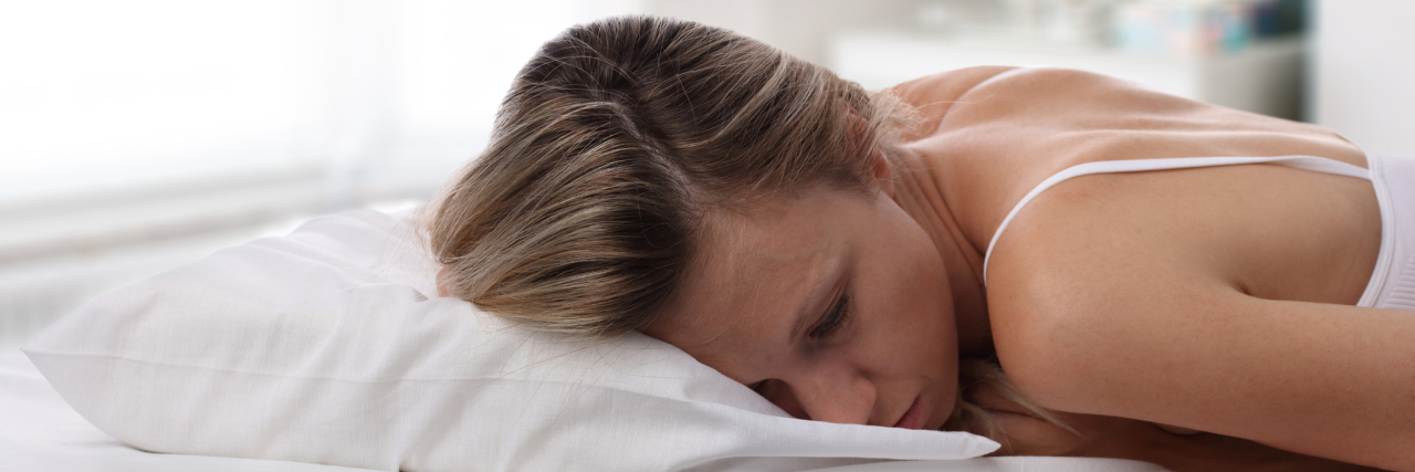 woman with depression lying face down in bed
