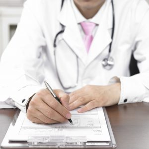 doctor writing on medical chart