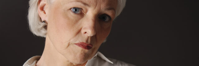 An older woman with a serious expression, looking into the camera.