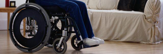 Woman sitting in wheelchair, looking towards windows, side view.