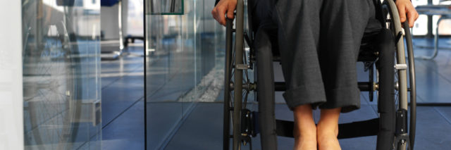 Businesswoman sitting in a wheelchair in an office.