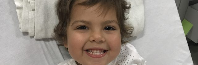 Young Girl with Cancer Smiling in Hospital Bed