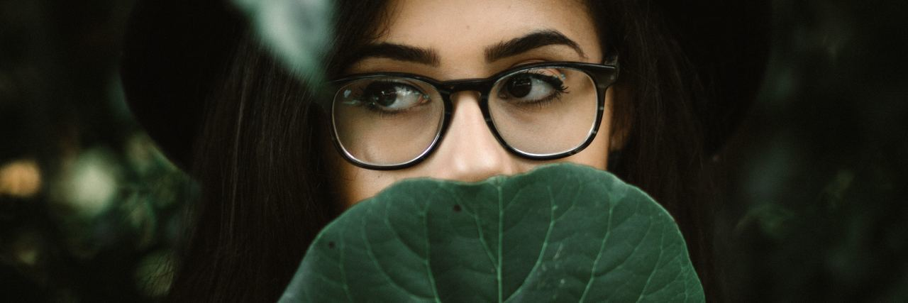 woman wearing glasses covering face with leaf