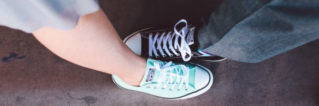 man and woman wearing converse sneakers in bright and dark color, feet facing opposite