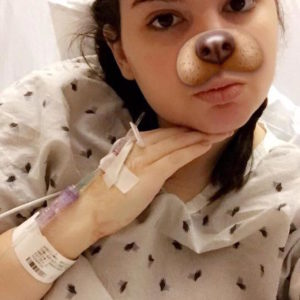 A girl in a hospital gown and bed, with a dog Snapchat filter on her face.