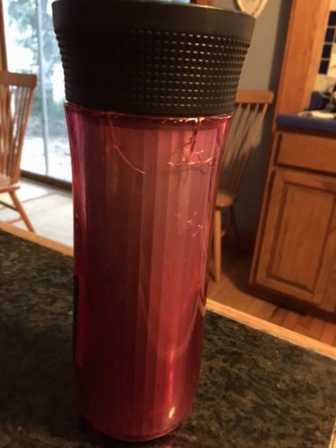 red broken travel mug with cracks in plastic