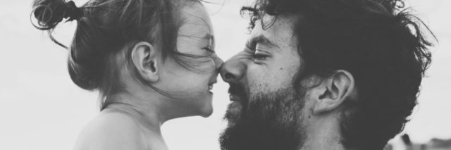 black and white photo of little girl and father nose to nose smiling