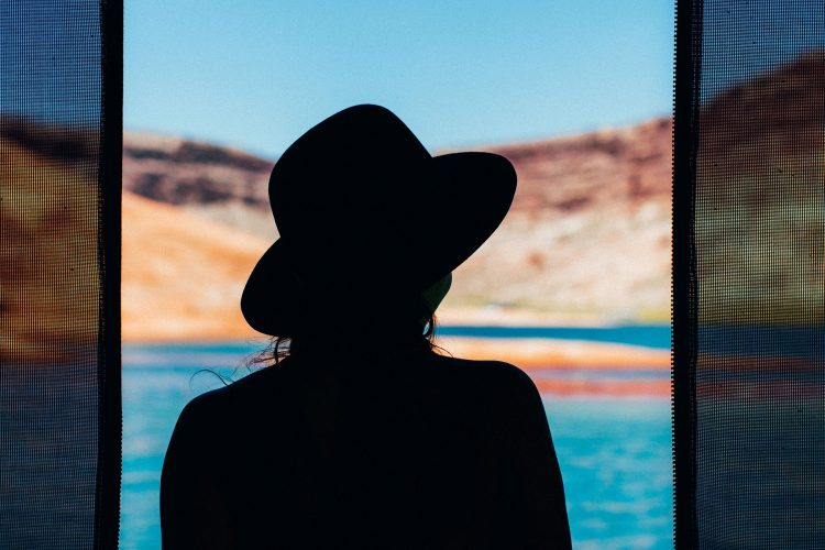 silhouette of a woman against a lake and red hills