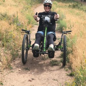 Michelle Hardy riding an adapted recumbent bike.