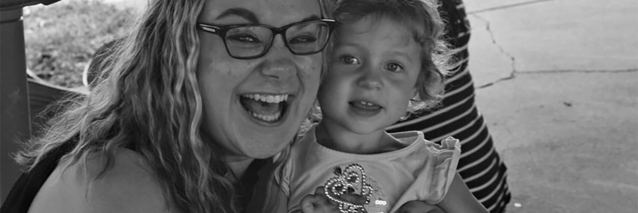 black and white photo of smiling woman next to young child