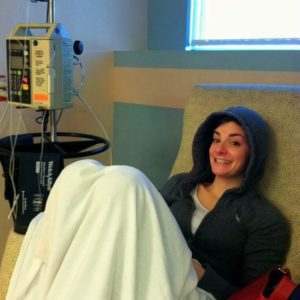 Woman sitting in a medical chair, with a blanket around her.