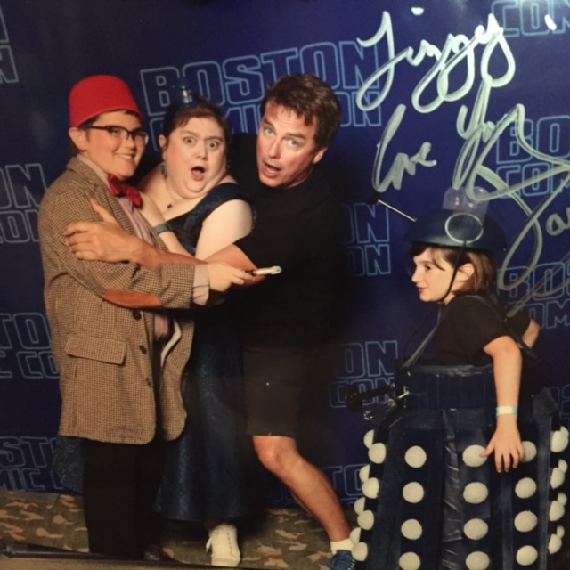 family posing with john barrowman at comic-con