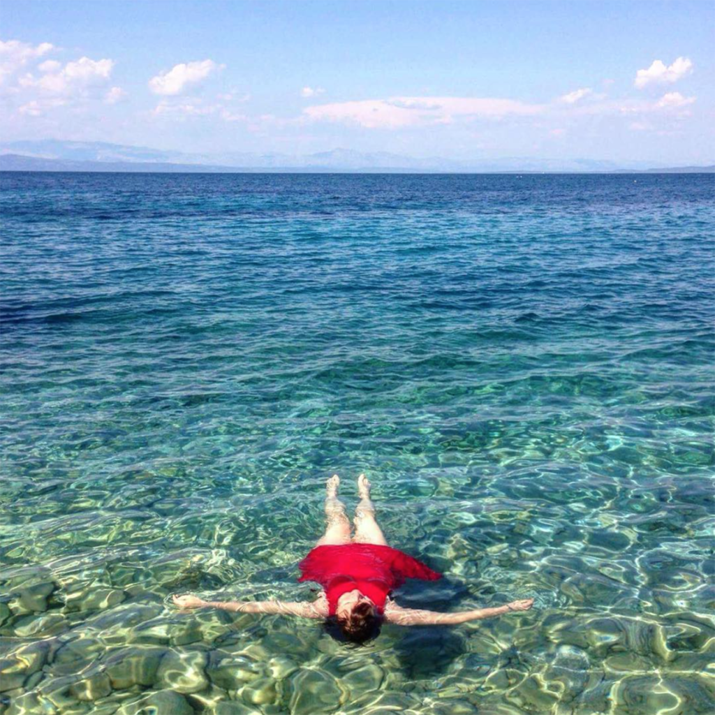 young woman lying in clear ocean wearing red bathing suit