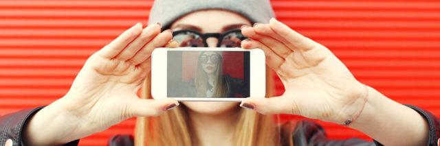girl taking photo of herself on smartphone