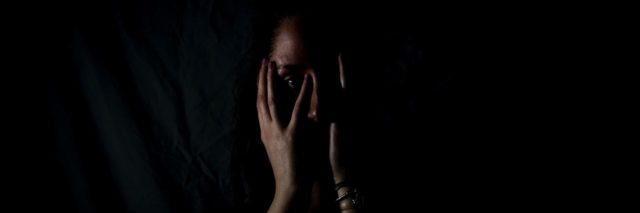 A woman stands in a dark room with her face covered