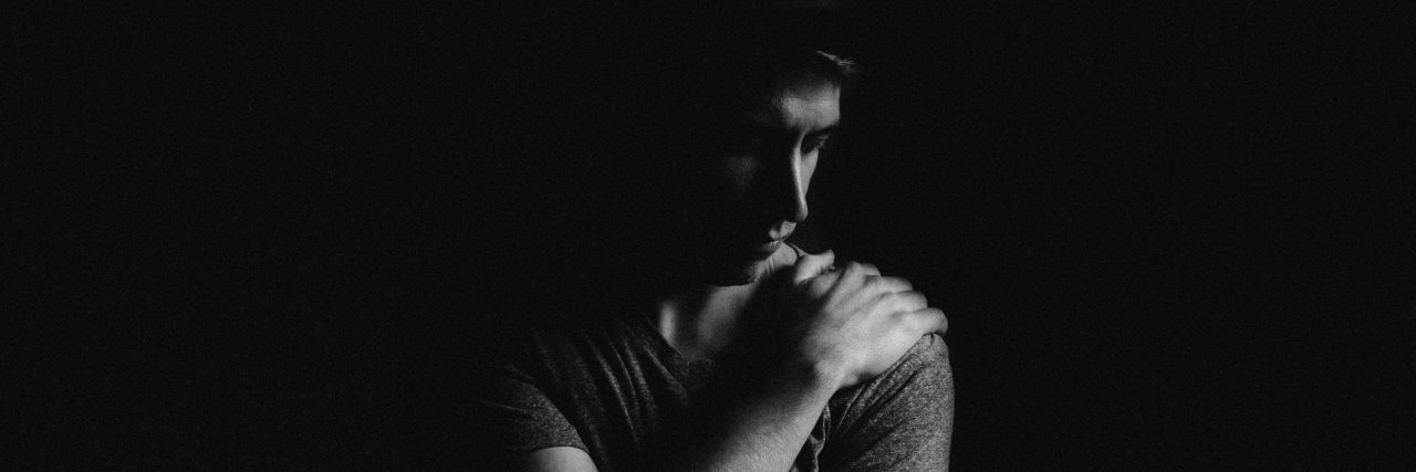 young man in darkness looking depressed anxious