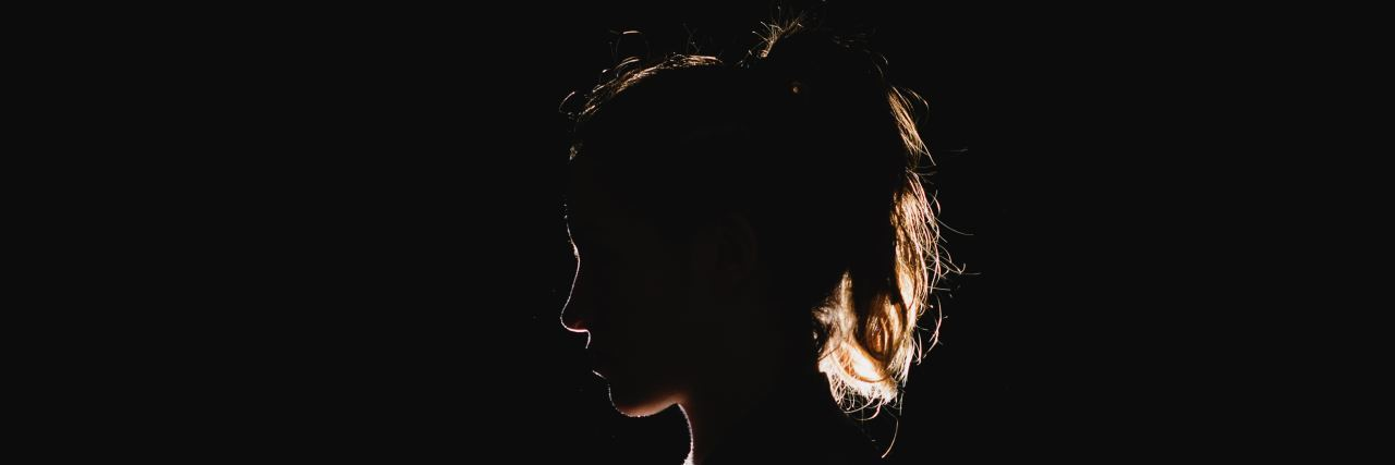 a woman's silhouette is outlined by light