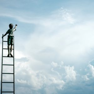 a child on a ladder reaching into the clouds
