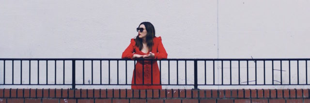 woman in red standing alone along railing