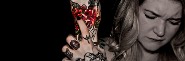 photo of woman with tattooes holding her wrist in pain