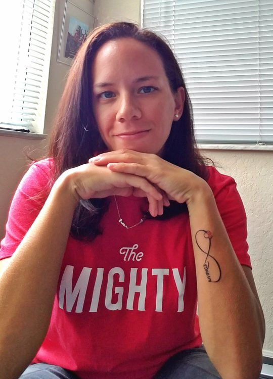 woman smiling and wearing 'the mighty' shirt with a tattoo on her arm