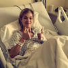 The writer of the article laying in a hospital bed, giving two thumbs up.