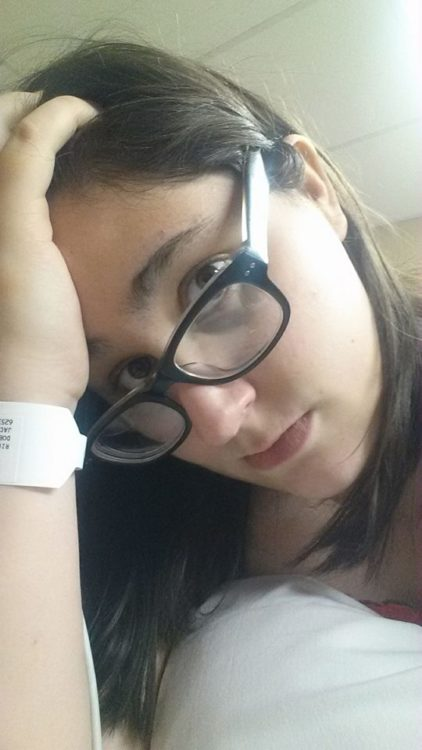 woman wearing glasses and a hospital bracelet