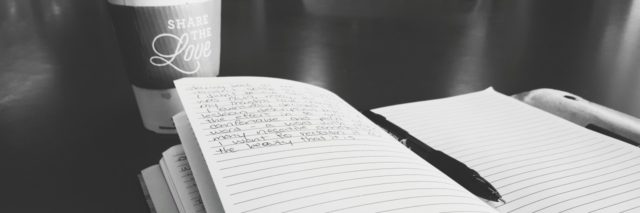 A journal and pen by a cup of coffee.