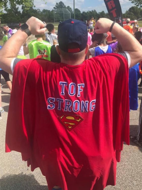 "The back of the writer, picturing him with a cape that reads, ""TOF strong."""