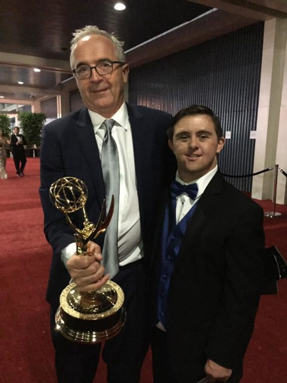 Bruce and Sean wearing tuxes, posing for the camera. Bruce holding an Emmy.
