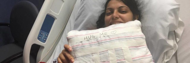 the author in a hospital bed, holding a pillow that says hug me