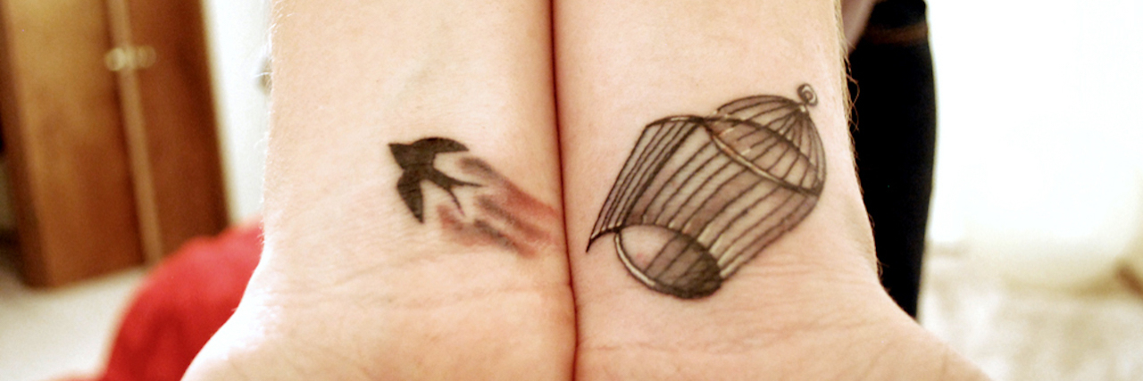 tattoo of bird escaping from cage on girls wrist