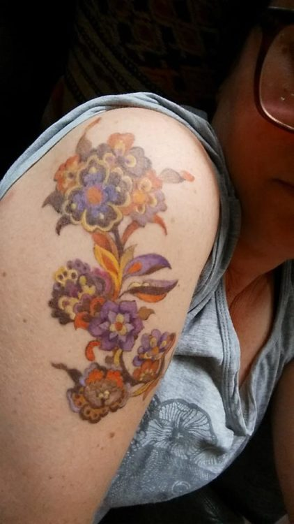 tattoo of orange and purple flowers