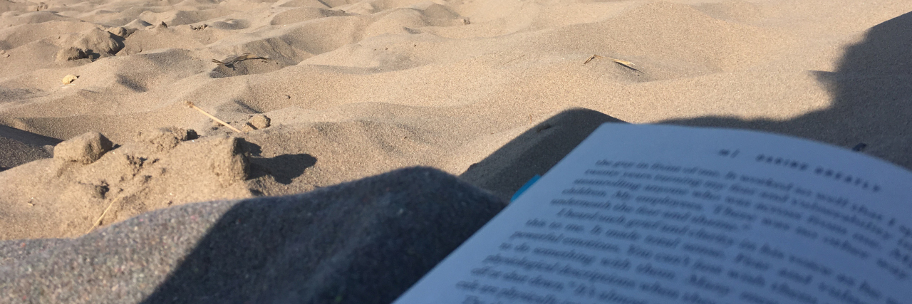 close up of book lying on beach in the shade with sea in background